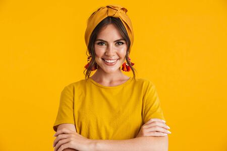 Portrait of a pretty cheerful young girl casually dressed standing isolated over yellow background, arms folded Stock fotó