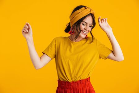 Portrait of a pretty cheerful young girl casually dressed standing isolated over yellow background, dancing