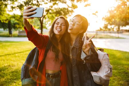 Image of two funny girls with tongues hanging out taking selfie photo on cellphone and gesturing peace sign while walking in green park