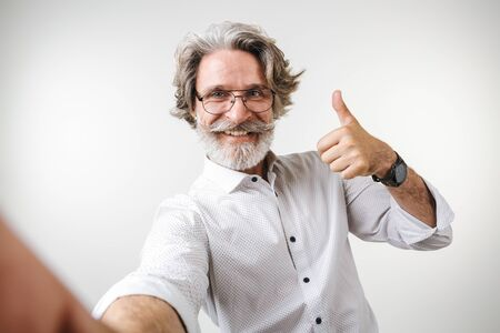 Portrait of a handsome happy mature businessman dressed in formal wear standing isolated over white
