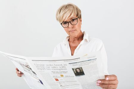 Portrait of uptight adult woman wearing eyeglasses reading newspaper isolated over white Banco de Imagens