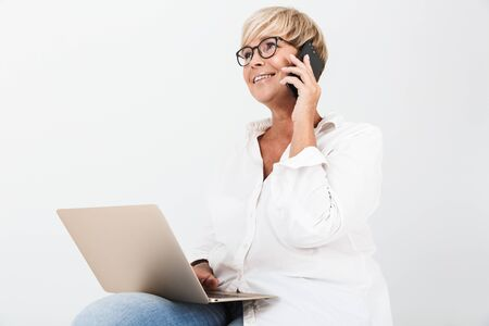 Image of gorgeous adult woman wearing eyeglasses talking on smartphone while sitting with laptop computer isolated over white background