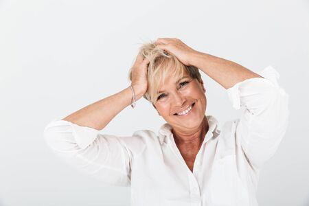 Porträt einer positiven erwachsenen Frau mit kurzen blonden Haaren, die ihren Kopf greift und in die Kamera lacht, isoliert auf weißem Hintergrund im Studio