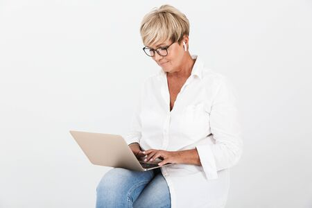 Image of pleased adult woman wearing eyeglasses and earpods sitting with laptop computer isolated over white background in studio