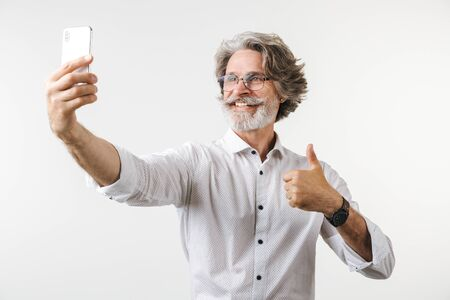 Portrait of a handsome happy mature businessman dressed in formal wear standing isolated over white background, taking a selfie, giving thumbs up