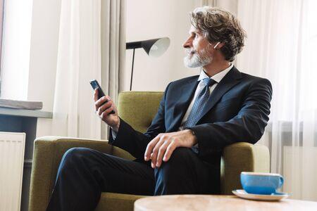 Foto eines ernsthaften, konzentrierten, bärtigen, reifen grauhaarigen Geschäftsmannes, der zu Hause auf einem Stuhl in der Nähe des Fensters in formeller Kleidung mit Mobiltelefon posiert. Standard-Bild