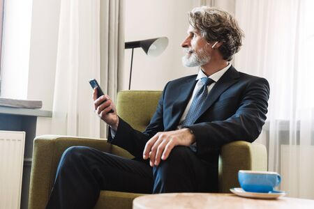 Photo of a serious concentrated bearded mature grey-haired businessman posing indoors at home sitting on chair near window dressed in formal clothes using mobile phone. Banco de Imagens
