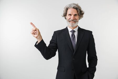 Smiling confident mature businessman wearing suit standing isolated over white background, pointing finger at copy space Stock Photo