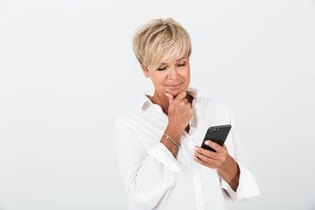 Portrait closeup of gorgeous adult woman with short blond hair thinking and holding cellphone isolated over white background in studio