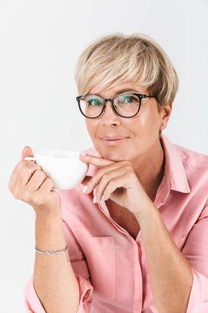 Porträt einer erwachsenen Frau mittleren Alters, die eine Brille trägt und die Kaffeetasse auf weißem Hintergrund lächelt und hält Standard-Bild