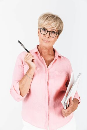 Portrait of caucasian adult woman wearing eyeglasses holding studying books and pen isolated over white background in studio 免版税图像