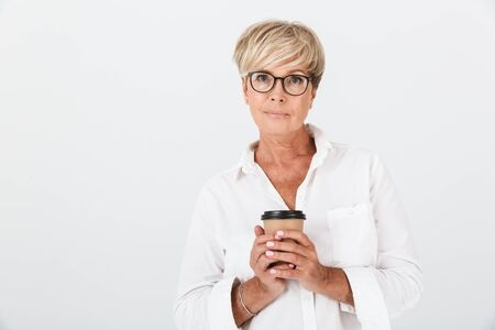 Portrait of confident adult woman wearing eyeglasses holding takeaway coffee cup isolated over white background in studio 免版税图像