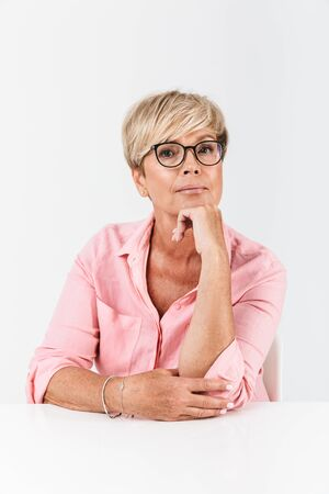 Portrait closeup of mature middle-aged woman with short blond hair looking at camera while sitting at table isolated over white background 免版税图像