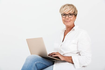 Bild einer zufriedenen erwachsenen Frau mit Brille, die lächelt, während sie mit Laptop-Computer sitzt, isoliert auf weißem Hintergrund im Studio?