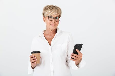 Portrait of caucasian adult woman wearing eyeglasses holding cellphone and takeaway coffee cup isolated over white background in studio