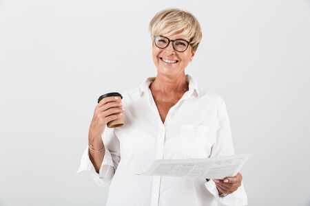 Portrait of joyous adult woman wearing eyeglasses holding takeaway coffee cup and reading newspaper isolated over white background