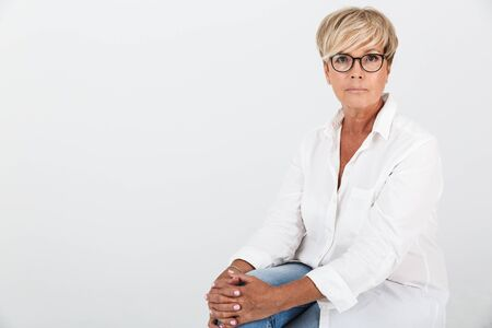Image of caucasian adult woman wearing eyeglasses looking at camera while sitting isolated over white background in studio 免版税图像