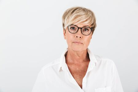 Portrait of caucasian adult woman wearing eyeglasses looking at camera isolated over white background in studio