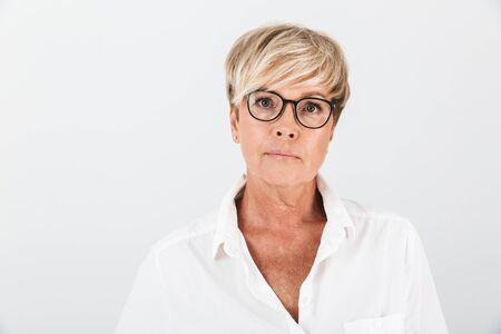 Retrato de mujer adulta caucásica con anteojos mirando a cámara aislada sobre fondo blanco en estudio
