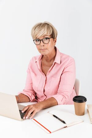 Portrait of confident middle-aged woman with short blond hair wearing eyeglasses using laptop computer at table isolated over white background 免版税图像