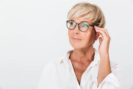 Portret van een mooie volwassen vrouw die opzij kijkt en haar bril aanraakt, geïsoleerd op een witte achtergrond in de studio Stockfoto