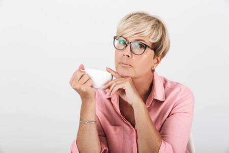 Portrait of concentrated middle-aged woman wearing eyeglasses looking at camera and holding coffee cup isolated over white background