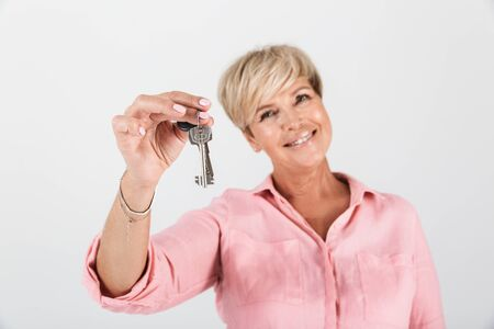 Portrait closeup of attractive middle-aged woman with short blond hair smiling and showing key isolated over white background in studio