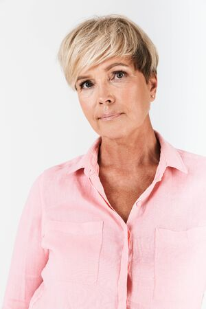 Portrait closeup of serious middle-aged woman with short blond hair looking at camera isolated over white background in studio