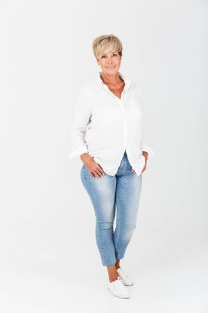 Porträt in voller Länge Nahaufnahme einer Frau mittleren Alters mit kurzen blonden Haaren, die im Studio isoliert auf weißem Hintergrund in die Kamera schaut Standard-Bild