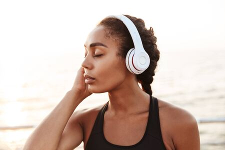 Image of calm pretty woman in sportive clothes with headphones standing by seaside in morning