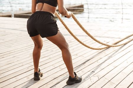 Cropped image of muscular young woman in sportive clothes doing workout with battle ropes by seaside in morning Stockfoto