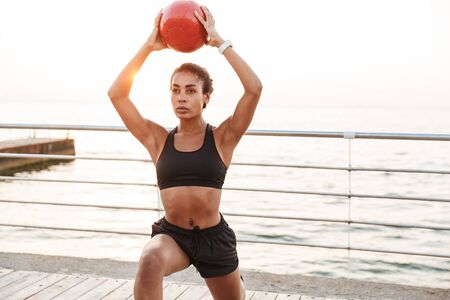 Image of athletic woman in sportive clothes squatting with fitness ball while doing workout by seaside in morning