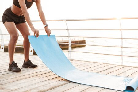 Image of young woman wearing sportive clothes putting finess mat on wooden floor by seaside in morning