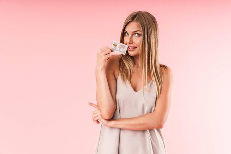 Bild Nahaufnahme einer schönen blonden Frau, die lächelt und mit dem Finger auf das Exemplar zeigt, während sie die Kreditkarte im Studio isoliert über Rosa hält?