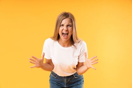 Image of negative stressed woman wearing casual t-shirt screaming and gesturing at camera isolated over yellow   in studio