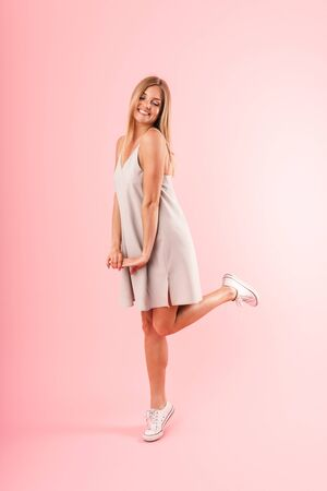 Full length image of modest blond woman wearing dress smiling and posing at camera isolated over pink  in studio