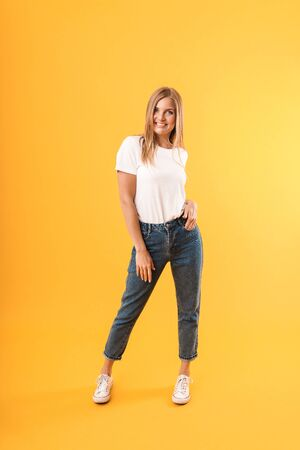 Full length image of caucasian blond woman wearing casual t-shirt smiling at camera isolated over yellow  in studio