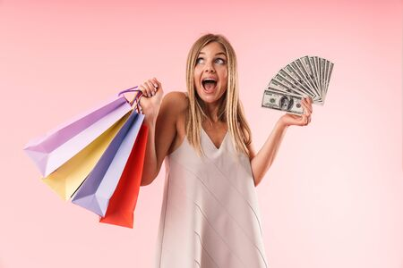 Image of young blond woman smiling while holding colorful paper shopping bags and money bills isolated over pink  in studio