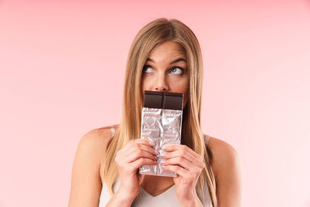 Image of charming blond woman wearing dress looking upward while holding chocolate bar at her mouth isolated over pink  in studio Reklamní fotografie