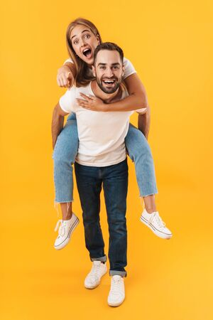 Image of caucasian couple in basic clothes pointing finger at camera while doing piggyback ride isolated over yellow Foto de archivo - 130811763