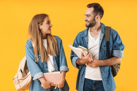 Image of beautiful students in denim clothes smiling while holding exercise books isolated over yellow Foto de archivo - 130811774