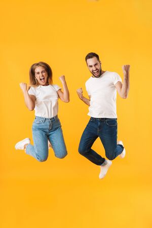 Image of happy couple man and woman in casual clothes jumping while celebrating victory isolated over yellow Foto de archivo - 130811775