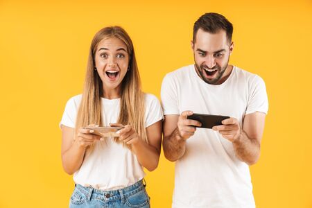 Image of pleased couple man and woman in basic t-shirts playing video games on smartphones together isolated over yellow Foto de archivo - 130811441