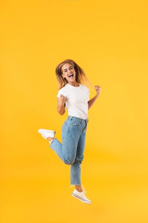 Full length image of amazed woman wearing casual clothes jumping and screaming like winner isolated over yellow