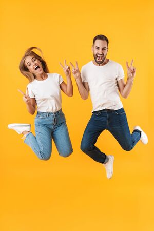 Image of cheerful couple man and woman in basic t-shirts jumping and showing peace sign at camera isolated over yellow
