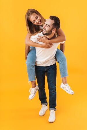 Image of beautiful couple man and woman in basic clothes smiling together while doing piggyback ride isolated over yellow Foto de archivo - 130811449