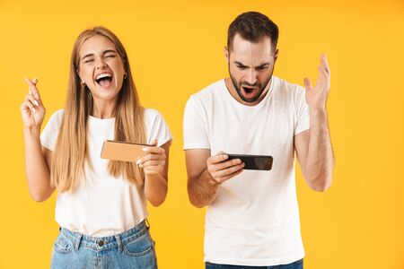 Image of funny couple man and woman in basic t-shirts playing video games on smartphones together isolated over yellow Foto de archivo - 130811451