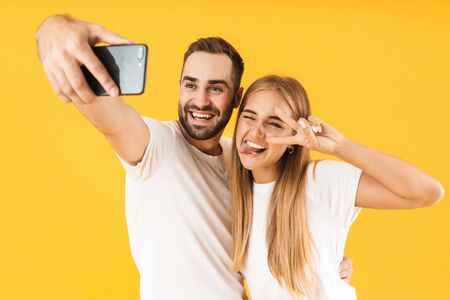 Image of happy couple in denim clothes showing peace sign while taking selfie photo on cellphone isolated over yellow Reklamní fotografie