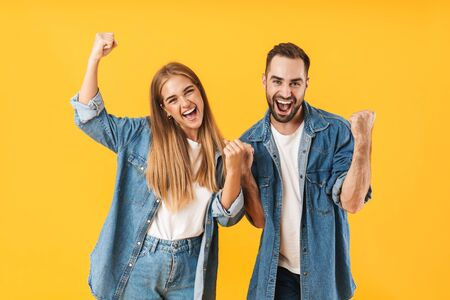 Image of happy couple man and woman in denim clothes rejoicing while celebrating victory isolated over yellow