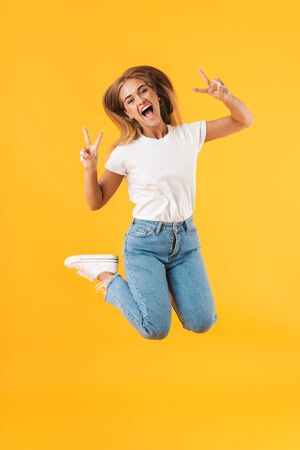 Full length image of delighted woman wearing casual clothes jumping and showing peace sign isolated over yellow Reklamní fotografie